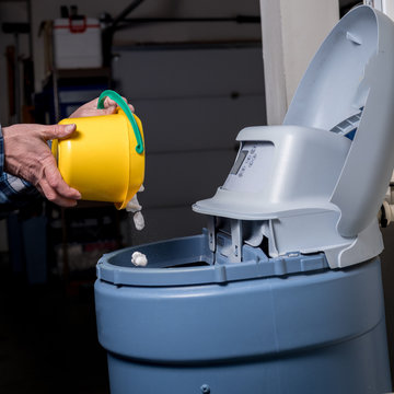 Yellow bucket pours salt pellets by a man into a water softener