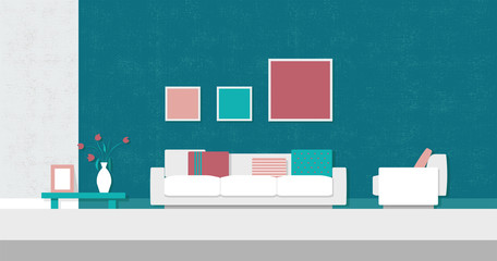 Cozy modern living room with white couch and chair, colorful cushions, paintings, table with flowers and turquoise grungy textured wall