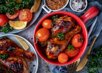 baked chicken legs in a barbecue sauce with tomatoes in a red frying pan, top view