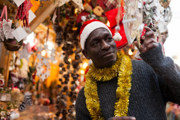 Man in Santa hat looking for New Year decorations