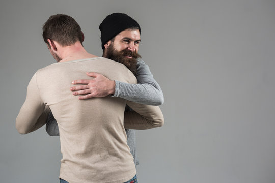 True friendship. Happy men in friendly relations. Best friends greeting each other. Bearded man shaking hands and hugging male friend. Bonds of friendship. Meeting of old friends