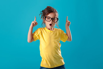 Cute surprised little girl in glasses and yellow t-shirt pointing up