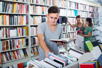 Portrait of  glad teenager looking at open book
