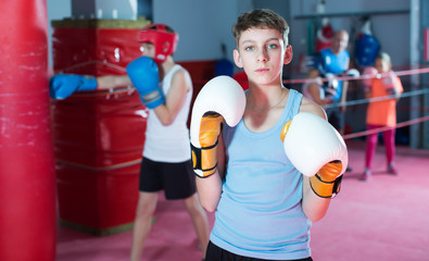 Young serious teenager with boxing gloves posing