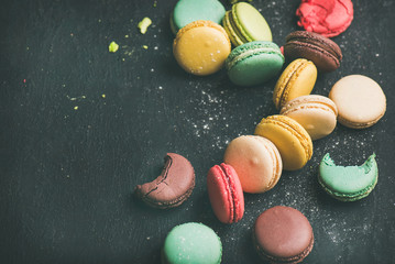 Autocollant pour porte Macarons Sweet colorful French macaroon cookies variety with sugar powder over black background, top view, selective focus, copy space