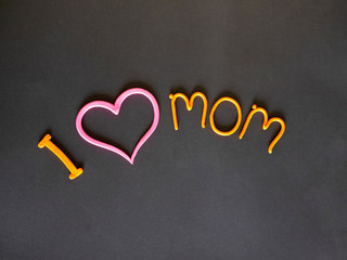 I love my mother the inscription of yellow plasticine with a pink heart