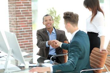 business partners shaking hands in the office.