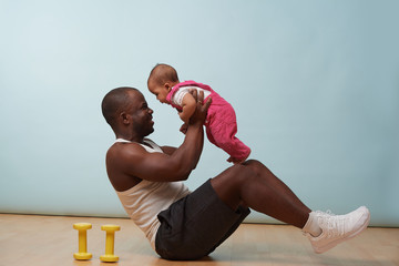 Father is doing crunches, using his baby daughter as additional weight