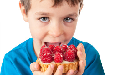 Little boy eating cakes with fruits