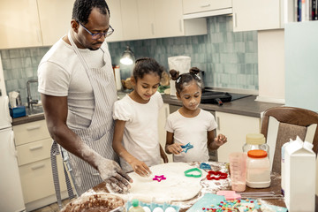 Two daughters feeling amazing while making cookies with father