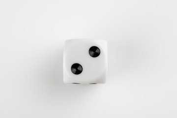 Single white with black dots dice on a white background, showing number two