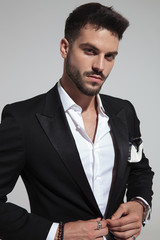 portrait of handsome fashion man buttoning black suit