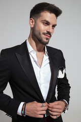 smiling handsome man buttoning black suit looks to side
