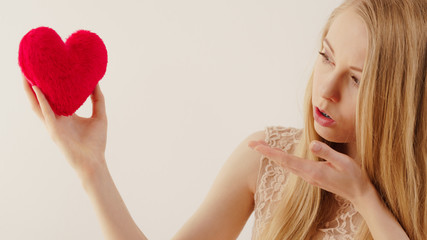 Young woman in love blowing kisses to heart