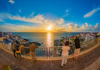 Group of people watching amazing sunset reflected in Atlantic ocean over the coast of Puerto de Santiago in Tenerife island, Spain