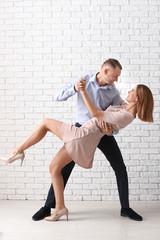 Beautiful couple dancing near white brick wall