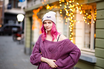 portrait of beautiful young girl with pink hair and purple sweater on city lights background.