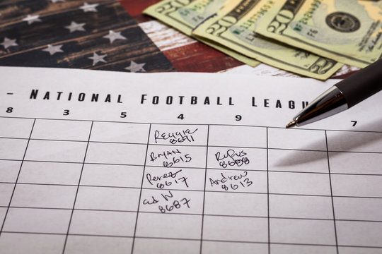 Football office pool grid for sports betting concept with money and a pen, partially completed boxes
