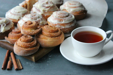 Beautiful fresh cinnamon rolls close-up on wooden grunge texture table. Fragrant homemade cakes, Cinnabon. A Cup of tea on a white saucer, cinnamon sticks. Delicious Breakfast buffet.