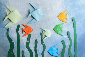 Composition with origami fishes on color background
