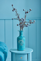Close up blue room and blue vase of plant, armchair and table style.