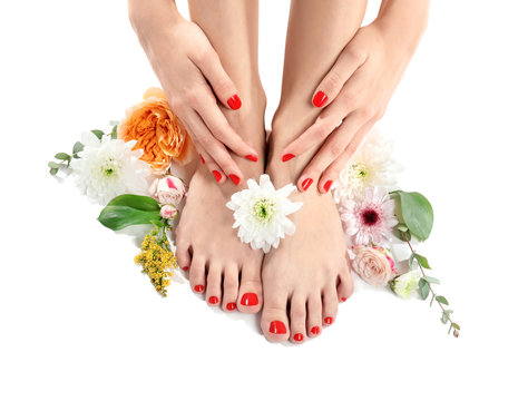 Young woman with beautiful pedicure and flowers on white background