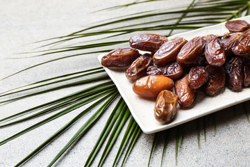 Plate with sweet dried dates on table