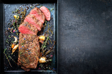 Traditional barbecue aged venison backstrap roast with herbs as top view on a rustic metal sheet with copy space right