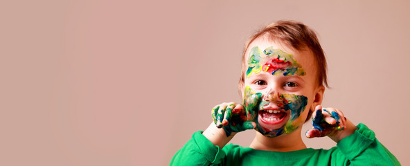 Art, creative and happiness childhood concept. Portrait of colorful painted hands and face in a beautiful young girl.
