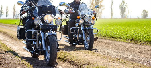 Deurstickers Motorsport Two Motorcycle Drivers Riding Custom Chopper Bikes on an Autumn Dirt Road in the Green Field. Adventure Concept.