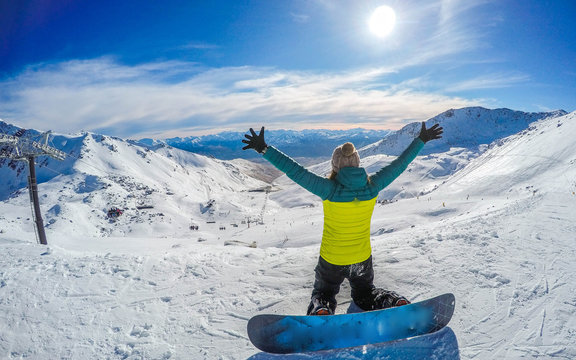 Winter sport activity.Woman holding snowboard, overlooking mountain landscape freedom, enjoying a winter, cold season. Having fun on the snow, mountains, ski area, Remarkables, New Zealand, Queenstown
