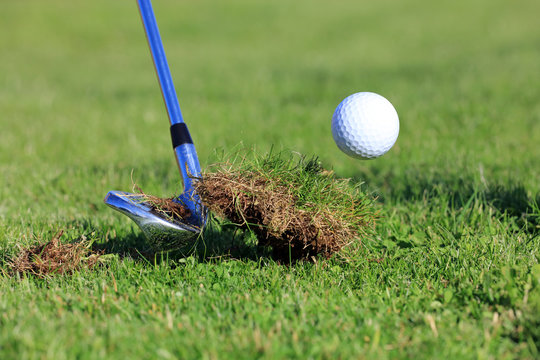 chipping golf ball out of the rough grass with a big divot
