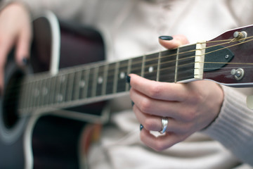 girl with black nails playing guitar strings
