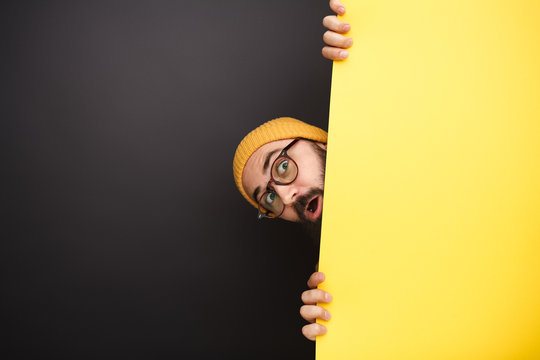 Funny man peeking out from behind yellow banner