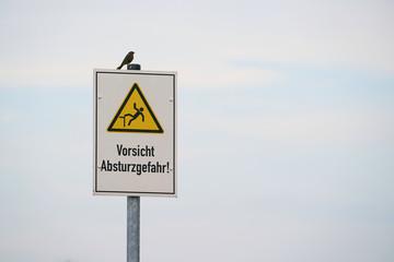 """Schild mit der Aufschrift """"Vorsicht Absturzgefahr"""". Auf dem Schild sitzt ein Vogel."""