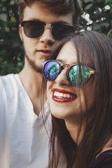 Stylish hipster couple in sunglasses smiling and making cool selfie. Happy family couple in love making self portrait and laughing in evening summer city. Vacation  and travel together