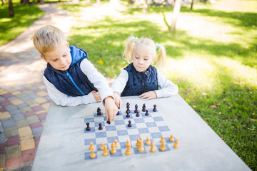 The topic children learning, logical development, mind and math, miscalculation moves advance. large family brothers and sister Caucasian boys and girl playing chess park bright sunny weather autumn Wall mural