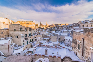 panoramic view of typical stones Sassi di Matera and church of Matera 2019 under blue sky with clouds and snow on the house, concept of travel and christmas holiday,capital of europe culture 2019