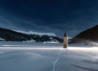 Wintery scene - frozen lake with sunken church tower under star-speckled sky