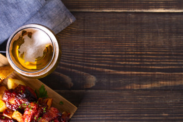 Tuinposter Bier / Cider Glass of beer and grilled pork spare ribs with fry, tasty snack to beer. Beer and food concept. Ale and meat. View from above, top studio shot, copy space
