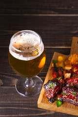 Glass of beer and grilled pork spare ribs with fry, tasty snack to beer. Beer and food concept. Ale and meat