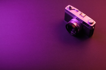 vintage camera isolate on black background and purple light. Space text