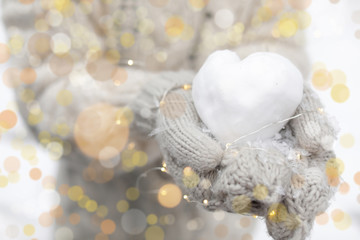 Woman holding Christmas lights and heart made of snow, closeup