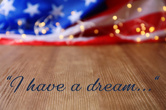 Blurred American flag and garland on wooden table. Space for text