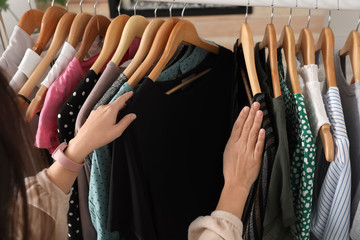 Woman choosing clothes from wardrobe rack, closeup