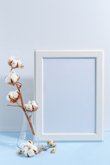 Mock up white frame and dry cotton twigs in vase on book shelf or desk. White-blue colors. Minimalistic concept.
