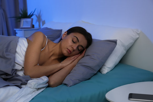 Young woman sleeping on soft pillow at night. Bedtime