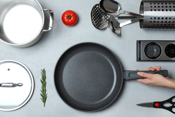 Woman holding frying pan over table with clean cookware, top view