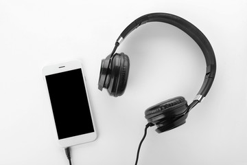 Smartphone with blank screen and headphones on white background, top view