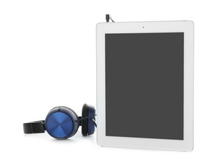 Tablet with blank screen and headphones on white background